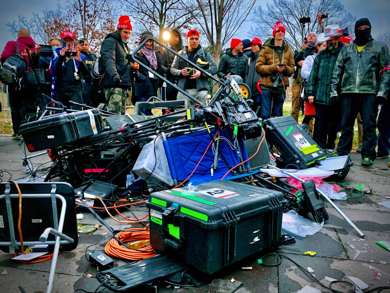 Trump supporters stand next to media equipment destroyed during the protest outside the Capitol.