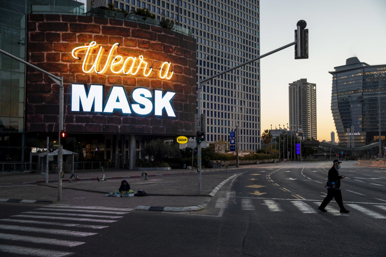 Image: A man crosses a road next to a billboard calling for people to wear masks during a nationwide lockdown following the government's measures to help stop the spread of the coronavirus in Tel Aviv, Israel,