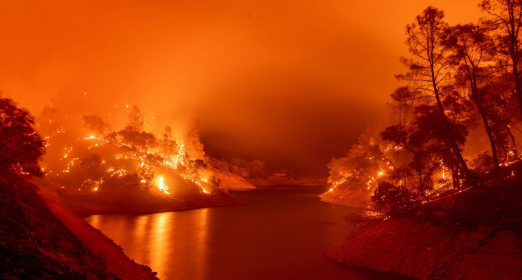 Image: Flames consumes both sides of a segment of Lake Berryessa during the Hennessey fire in the Spanish Flat area of Napa,