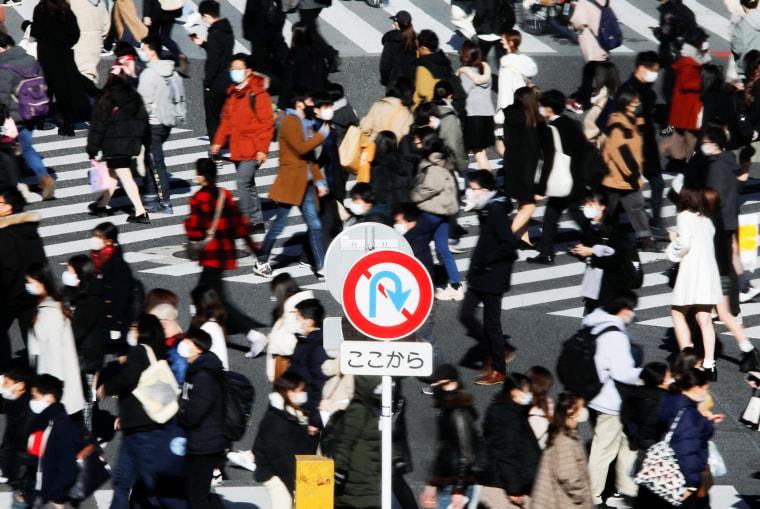 Image: Passersby wearing protective face masks walks at Shibuya crossing amid coronavirus disease (COVID-19) outbreak in Tokyo