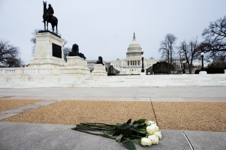 Image: Azhenedt Sanabria holds flowers as she pays her respects to late Capitol Police Officer Brian Sicknick
