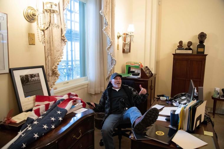 Richard Barnett sits in House Speaker Nancy Pelosi's office on Jan. 6, 2021.