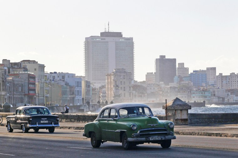 Image: Vintage cars drive on the seafront boulevard El Malecon in Havana