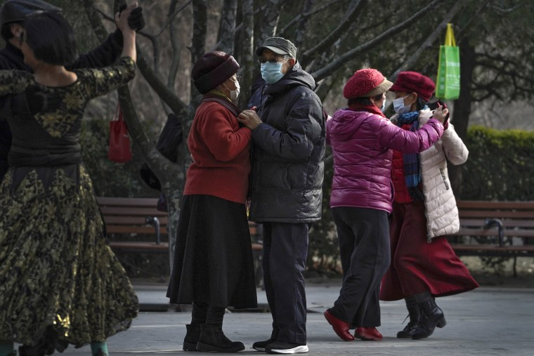 Image: People wearing face masks to help curb the spread of the coronavirus enjoy a social dance at a public park in Beijing