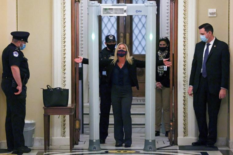 Image: U.S. Representative Marjorie Taylor Greene (R-GA) goes through a new metal detector to enter the House floor in Washington