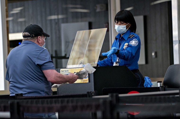 Image: A Transportation Security Administration (TSA) agent wears a protective mask and stands behind a protective barrier while screening a traveler at Ronald Reagan National Airport.