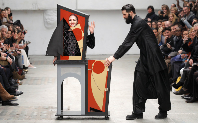 Image: FILE PHOTO: A magician performs with a model who presents a creation by Indian designer Manish Arora as part of his Fall-Winter 2011/2012 women's ready-to-wear fashion collection for French fashion house Guy Laroche during Paris Fashion Week