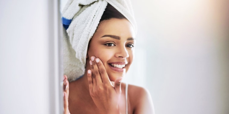 Woman rubbing facial toner on her face in the bathroom