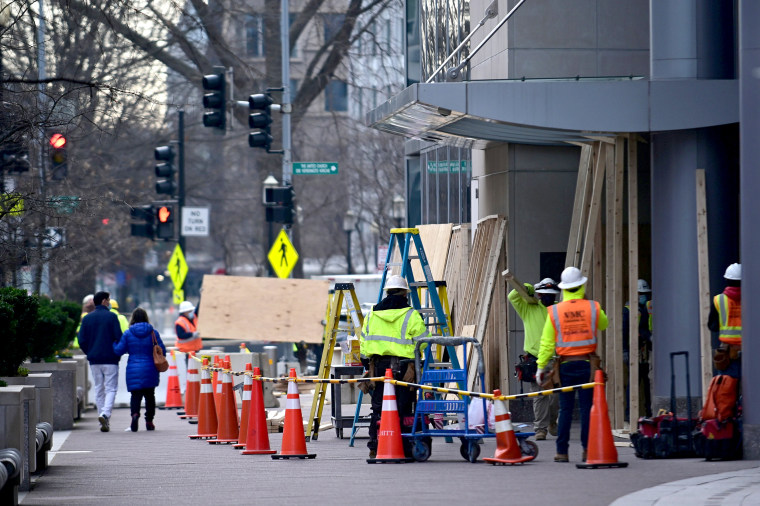 Image: Workers board up the buildings near the White House prior to the presidential inauguration in Washington