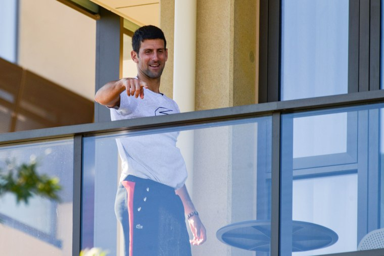 Image: Men's world number one tennis player Novak Djokovic of Serbia gestures from his hotel balcony in Adelaide, Australia o