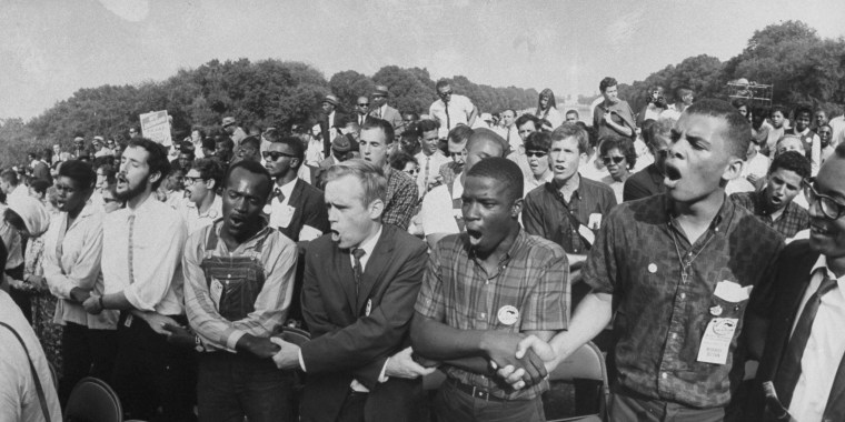 Image: Group of people holding hands during a civil rights rally in front of the Washington Monument.