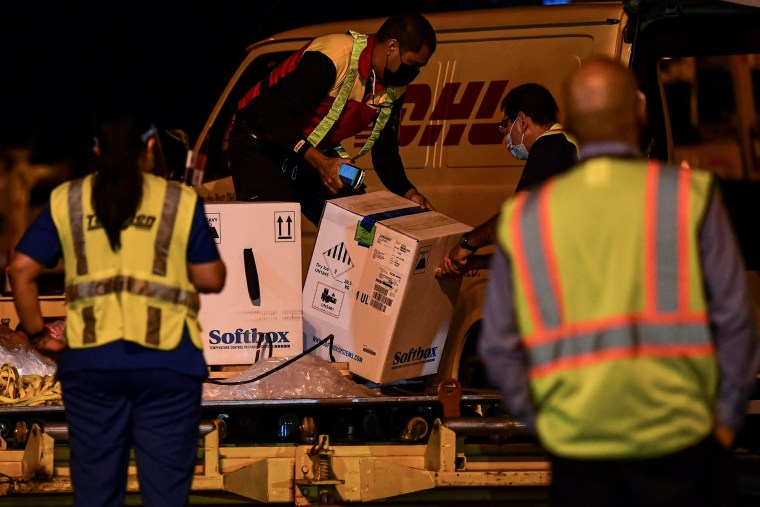 Image: Workers unload containers carrying the first shipment of the Pfizer/BioNTech Covid-19 vaccine for Panama, from a courier aircraft transporting some 12,840 doses of the vaccine into the country, at Tocumen International Airport in Panama City
