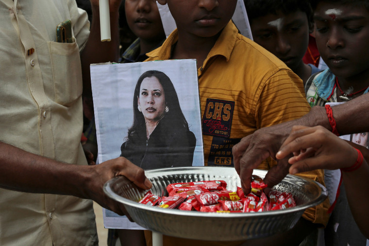 Image: A man holds a placard with the photo of Vice President-elect Kamala Harris as another distributes sweets during the celebration on the day of her inauguration in the village of Thulasendrapuram,