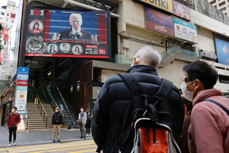 Image: People look at a TV screen showing news of President Joe Biden after his inauguration, in Hong Kong