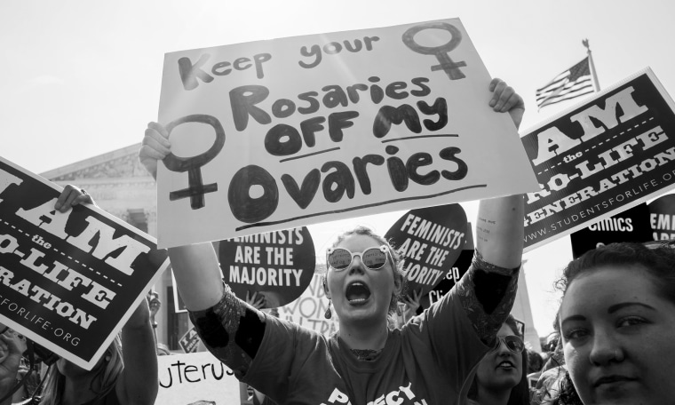 """Image: Pro-choice activist holds sign that reads,""""Keep your rosaries off my ovaries""""."""