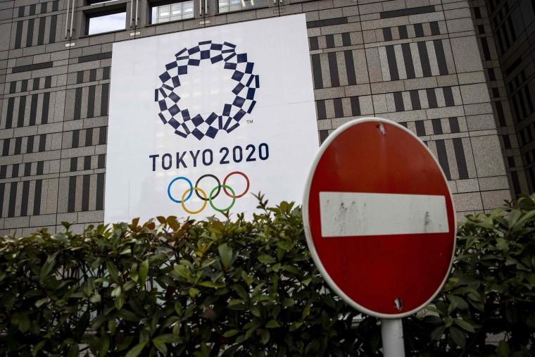 Image: A traffic sign is seen next to an official Tokyo 2020 Olympic Games banner hanging on the Tokyo Metropolitan Government Building