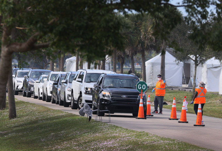 Department of Health workers direct traffic at a drive-thru vaccination site on Jan. 4, 2021 in Davie, Fla.