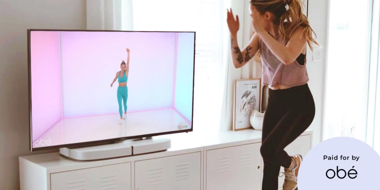Woman working out to an Ob? fitness class in her home