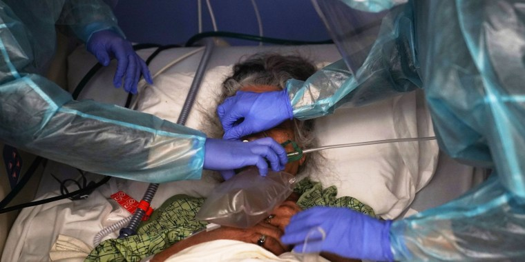 Two nurses put a ventilator on a patient in a Covid-19 unit at St. Joseph Hospital in Orange, Calif., on Jan. 7, 2021.