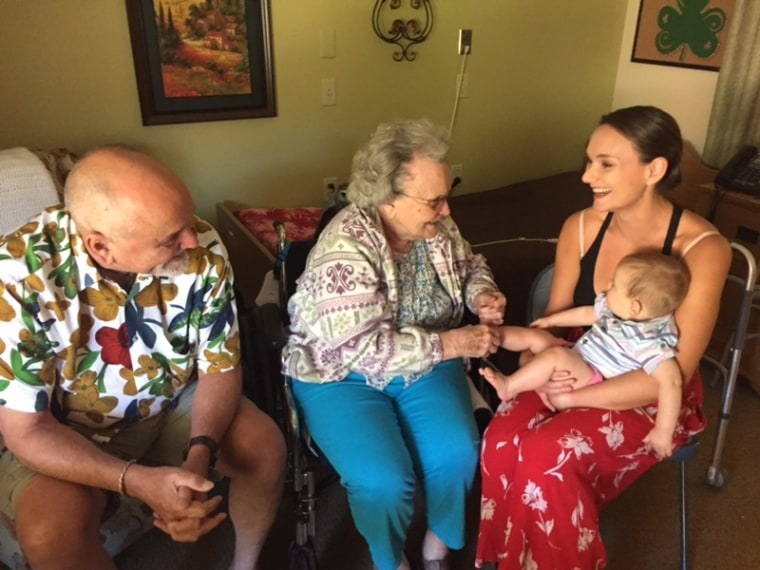 MaryAnn Zack, center, is pictured at the moment she met her grandson, Jack, for the first time. She later died of COVID-19 in a long-term care facility.