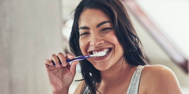 Woman brushing her teeth with teeth whitening products