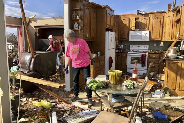 Patti Herring sobs as she sorts through the remains of her home in Fultondale, Ala., on Tuesday, Jan. 26, 2021, after it was destroyed by a tornado.
