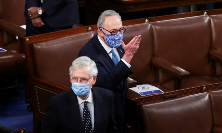 Image: Mitch McConnell faces left and Chuck Schumer behind him faces forward.