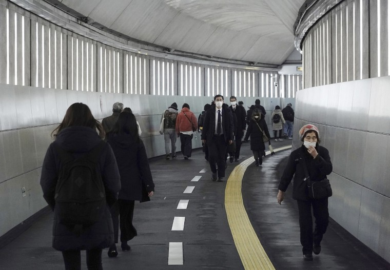 Image: People wearing protective masks to help curb the spread of the coronavirus walk along an underpass Tuesday, Jan. 26, 2021, in Tokyo.