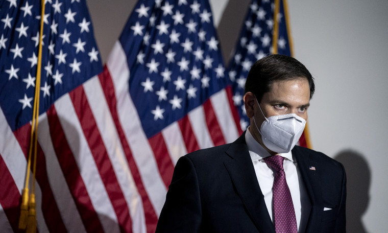 Image: Marco Rubio in a mask stands against U.S. flags