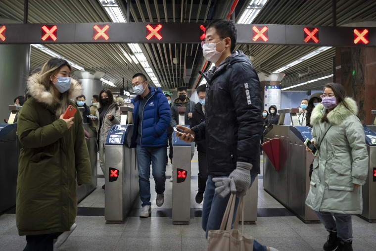 Image: People wearing face masks to protect against the spread of the coronavirus walk through a subway station in Beijing