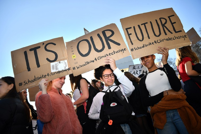 """Image: Young demonstrators hold placards as they attend a climate change protest organised by """"Youth Strike 4 Climate"""", opposite the Houses of Parliament in central London"""