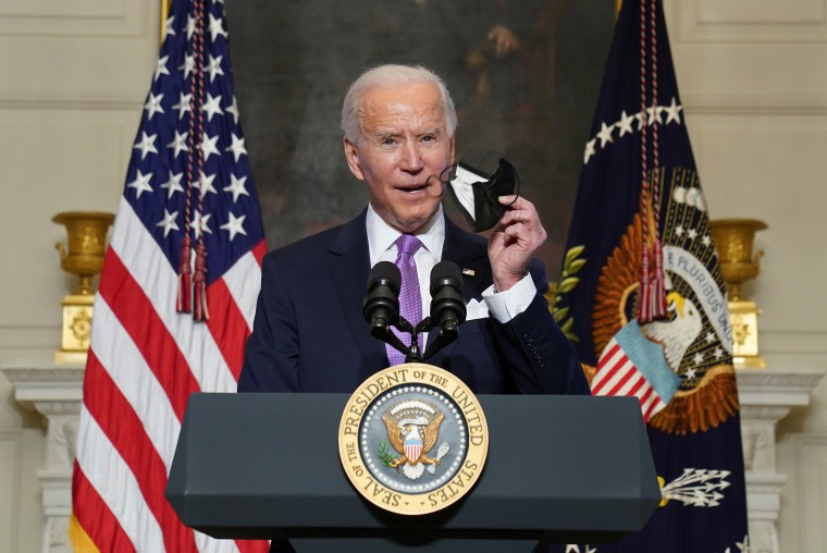Image:President Joe Biden holds up a face mask as he speaks about the fight to contain the Covid-19 pandemic, at the White House.
