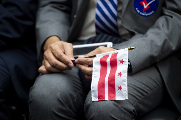 A man holds a Washington, D.C., flag during a House committee hearing on D.C. statehood on Feb. 11, 2020.