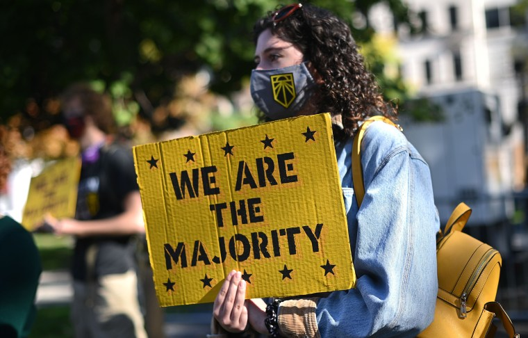 """Image: A girl holds a yellow placard that reads,""""We are the majority""""."""