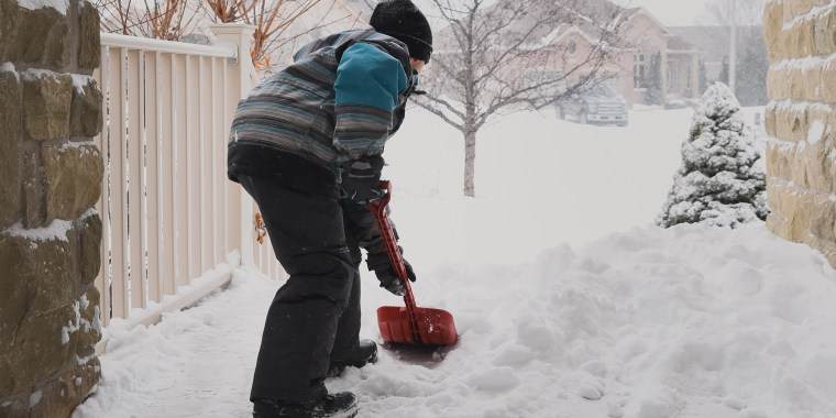 Young boy shovelling snow off of front steps during a snowstorm.