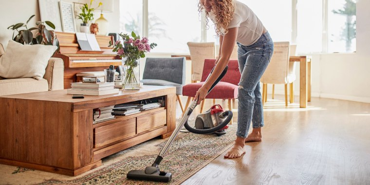 Woman vacuuming her living room with her heavy duty carpet cleaner