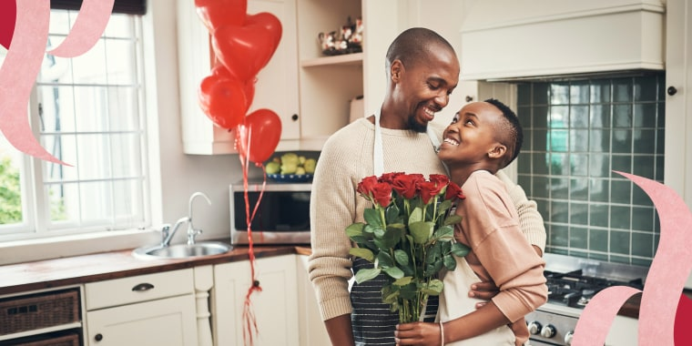 Couple in the kitchen holding a bouquet of flowers to celebrate Valentines day