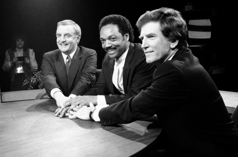 Image: Former Vice President Walter Mondale, Rev. Jesse Jackson, and Sen. Gary Hart clasp hands during a Democratic presidential debate in New York in 1984.