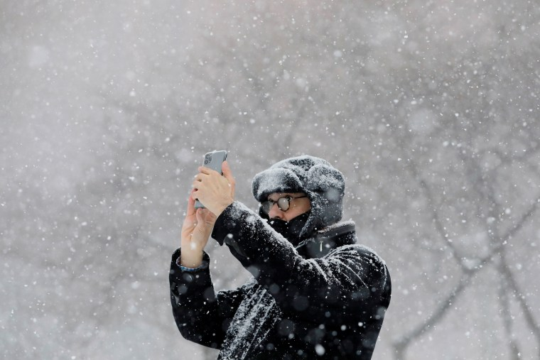 Image: A person uses a mobile phone at the Washington Square Park during a snow storm in New York