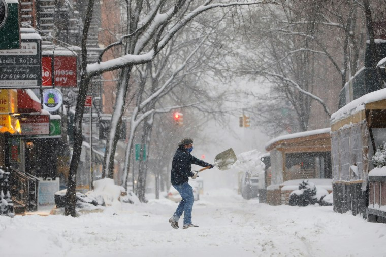 Image: A person shovels snow in the Greenwich Village neighborhood in New York