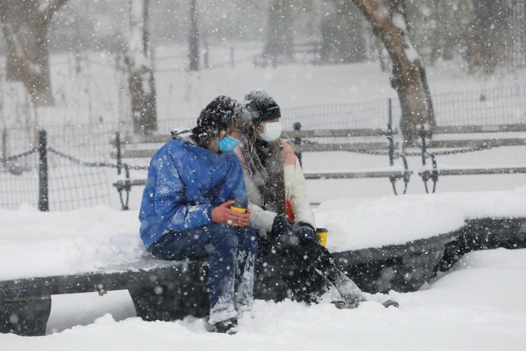 Image: People sit on a bench at the Washington Square Park during a snow storm in New York