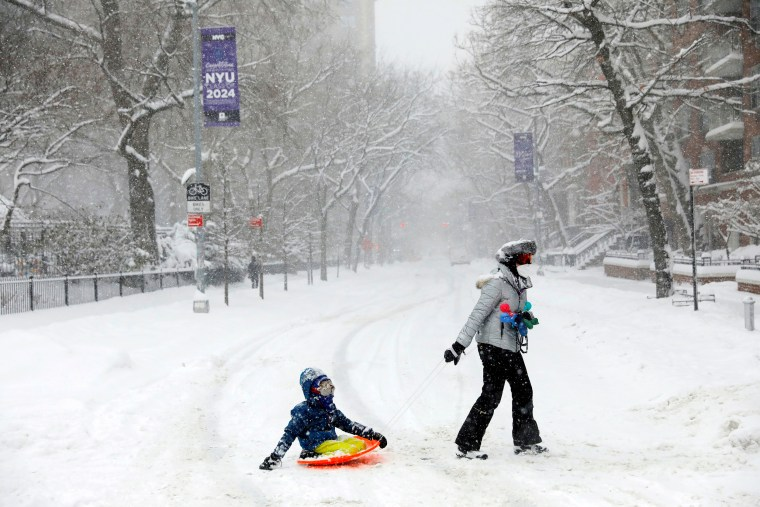 Image: A woman drags a child on a sledge near Washington Square Park during a snow storm in New York