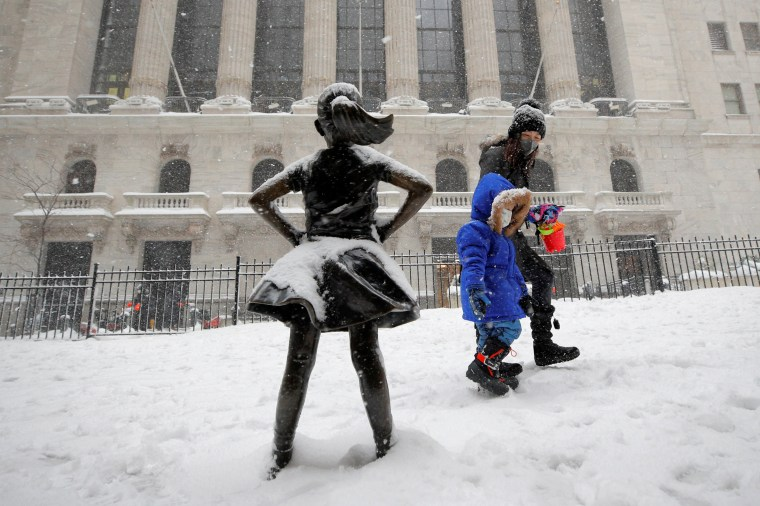"Image: The ""Fearless Girl"" sculpture is seen outside NYSE during a snow storm in New York"