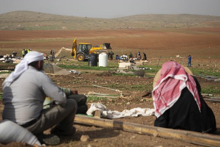 Image: Palestinian Bedouin watch Israeli troops demolish tents and other structures of Khirbet Humsu hamlet in Jordan Valley in the West Bank