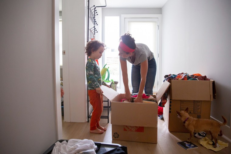 Image: Levi Benjamin-Brown, 5, helps him mother Kyala Brown unpack does of toys at their new home in El Cerrito, Calif