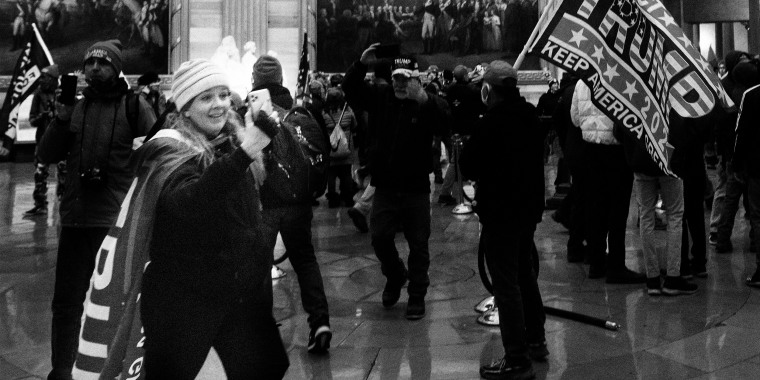 "Image: Jenny Cudd wearing a cape that reads, ""Trump"" takes a photo with her phone amidst other rioters at the US Capitol's Rotunda."