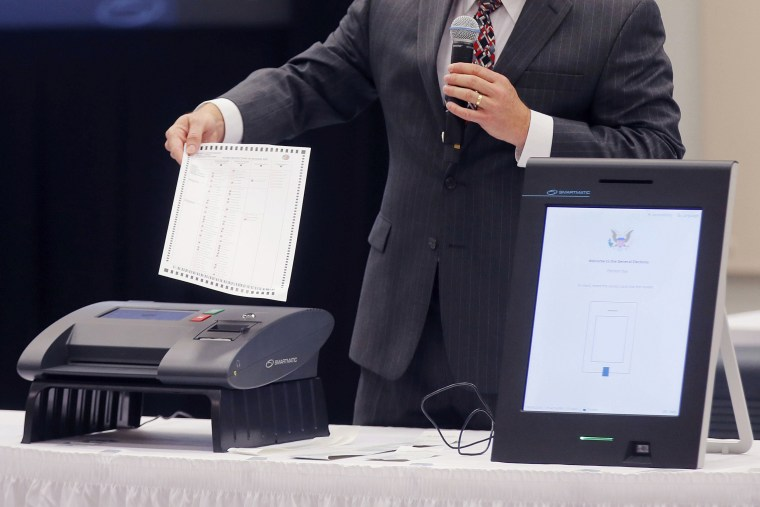A Smartmatic representative demonstrates his company's voting system in Grovetown, Ga., on Aug. 30, 2018.