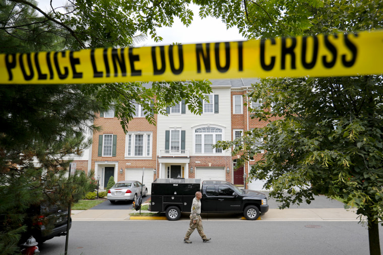 A law enforcement officer walks on the street outside the home of Nicholas Young, a Washington Metro Transit Officer, on Aug. 3, 2016, in Fairfax, Va.,