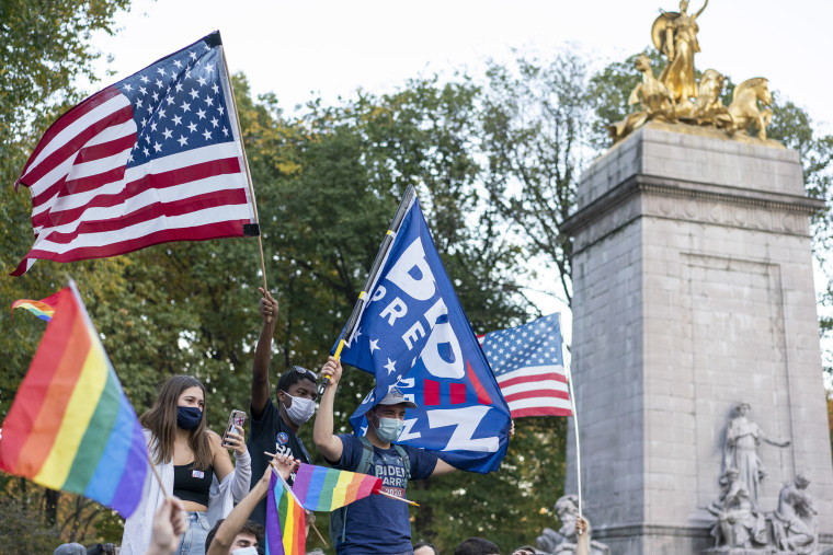 Image: People wave Biden for President, LGBTQ, and American flags near Columbus Circle.