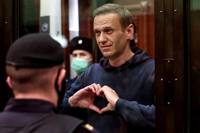 Russian opposition leader Alexei Navalny makes a heart shape with his hands from inside a glass cell during a court hearing in Moscow on Feb. 2, 2021.